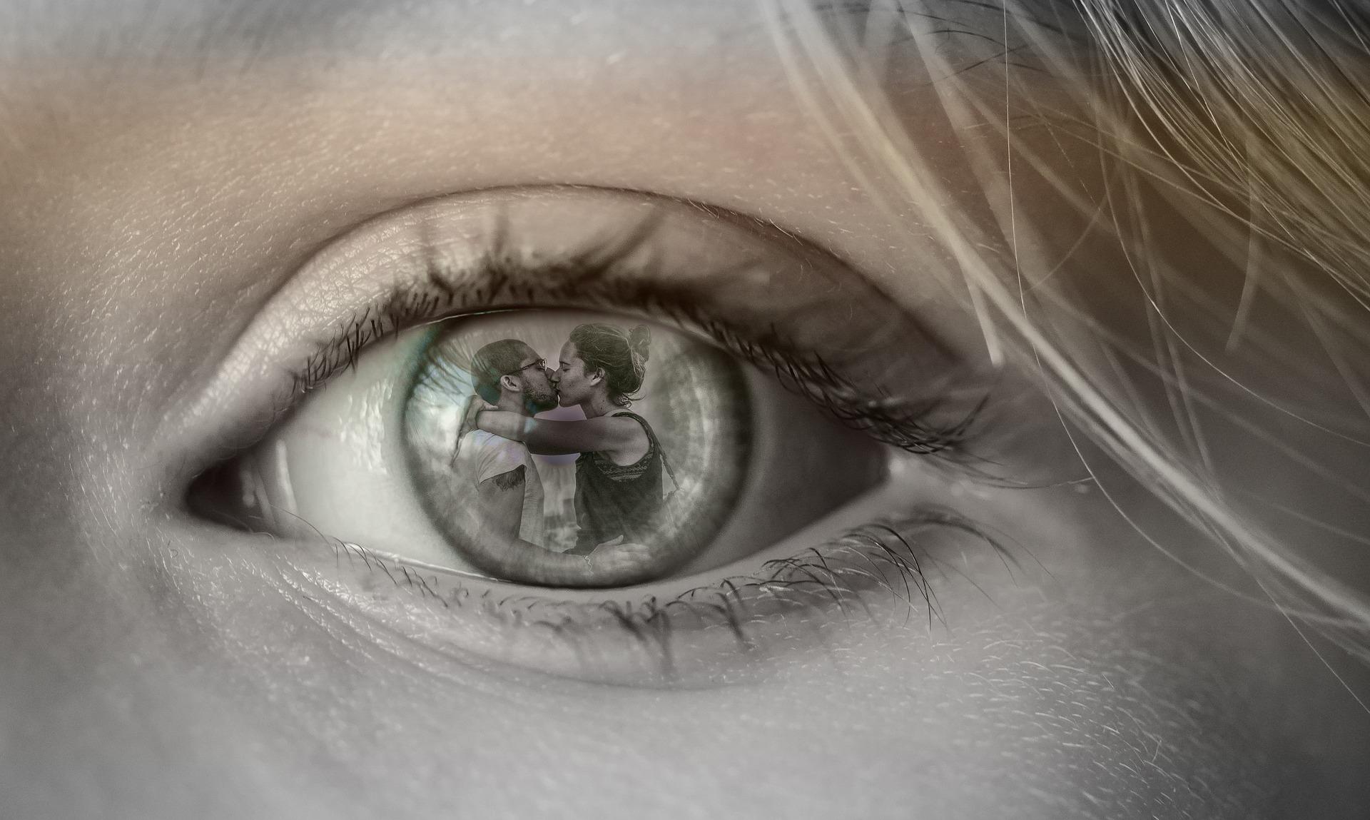 Olho de uma mulher refletindo a cena do namorado beijando outra mulher.